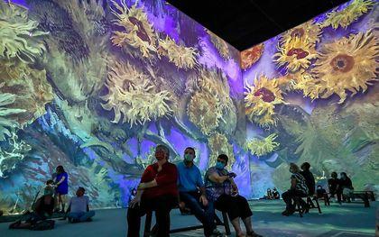 Mensen bezoeken de kunsttentoonstelling 'Van Gogh: The Immersive Experience' in de Pullman Yards in Atlanta, Georgia. De lopende tentoonstelling toont een licht- en geluidservaring van 20.000 vierkante meter van het werk van de Nederlandse post-impressionistische schilder Vincent van Gogh. beeld EPA, ERIK S. LESSER