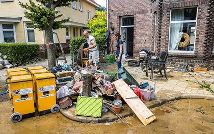 Inwoners ruimen puin na de wateroverlast in Valkenburg aan de Geul. beeld ANP, Marcel van Hoorn