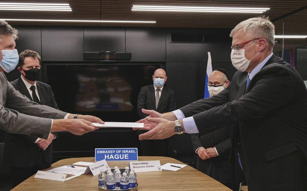 Overhandiging van de schuldbelijdenis aan de Israëlische ambassadeur Naor Gilon (rechts) en opperrabijn Binyomin Jacobs (achter Gilon). Links dr. H. J. Schouten en ds. C. P. de Boer. Ds. D. J. Diepenbroek kijkt toe.beeld Ambassade Israël