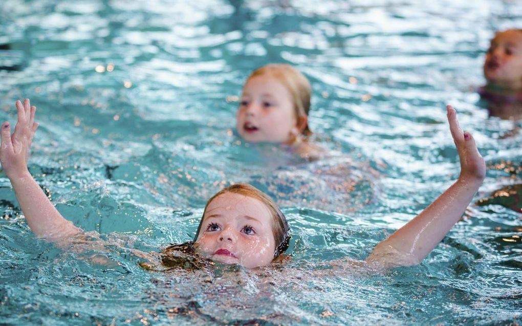 Kinderen doen in het zwembad dappere pogingen om te zwemmen. beeld ANP, Marco de Swart