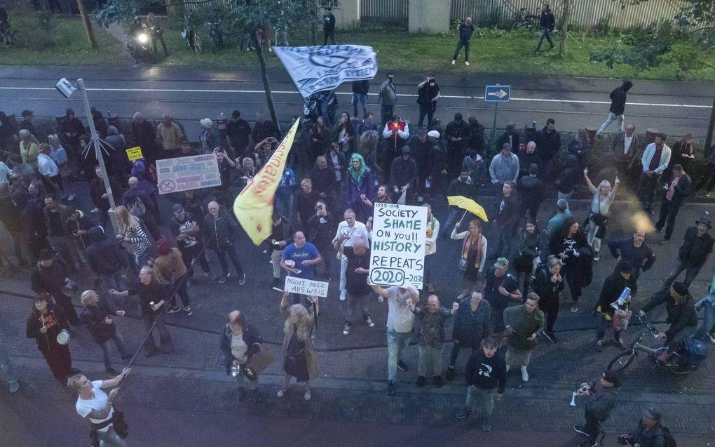 Demonstranten protesteren bij het ministerie van Justitie in Den Haag waar dinsdag de coronapersconferentie plaatsvond. Daarbij werd vuurwerk afgestoken.beeld ANP, Bart Maat