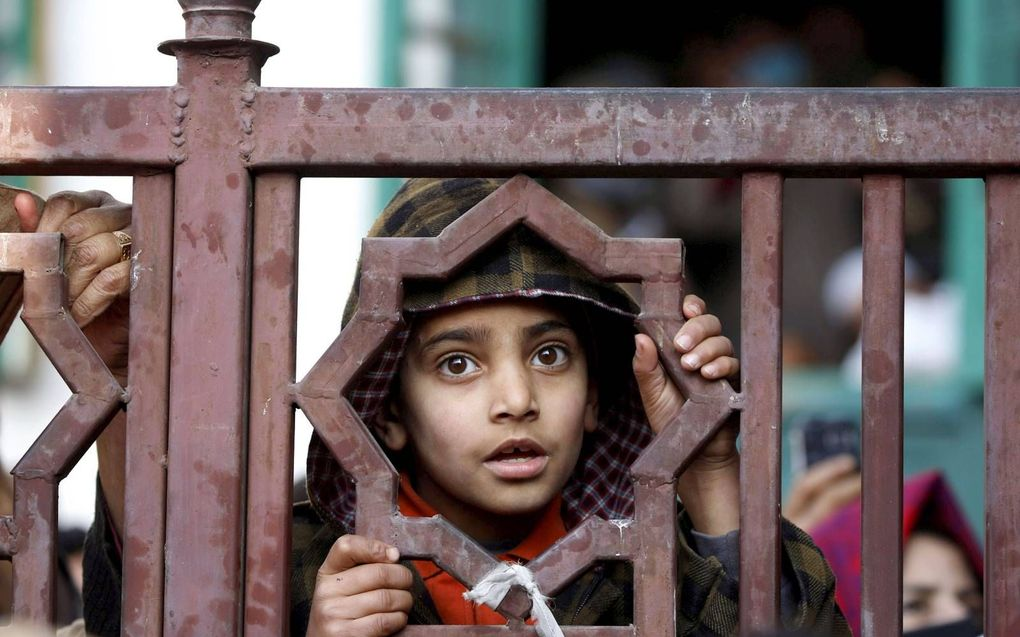 Een islamitisch jongetje in Srinagar, het Indiase deel van Kashmir, luistert naar een moslimgeestelijke.beeld EPA, Farooq Khan