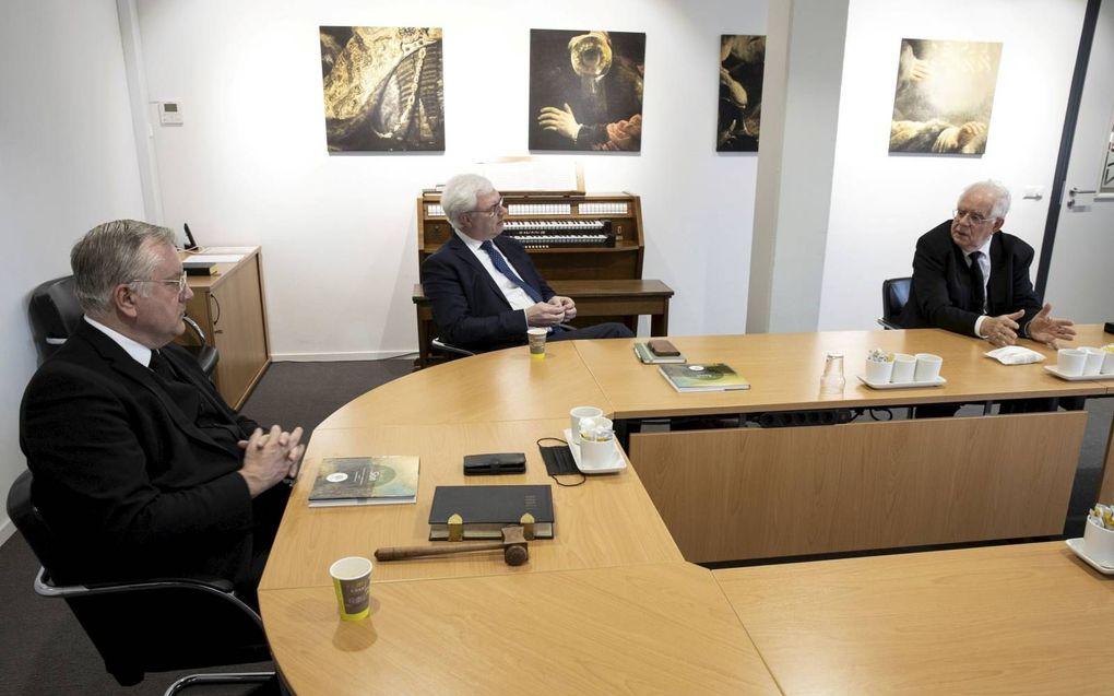 Ds. A. Schot (l.), J. J. de Jong (m.) en ds. C. J. Meeuse (r.) in gesprek over 25 jaar deputaatschap voor Israël van de Gereformeerde Gemeenten. beeld RD, Anton Dommerholt