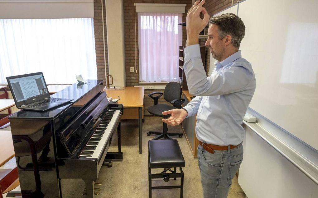 Muziekdocent Frans Nieuwenhuyzen van het Calvijn College oefent met zijn leerlingen uit vwo 5 verschillende dirigeertechnieken. beeld Dirk-Jan Gjeltema