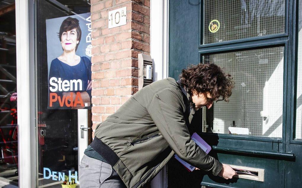 GroenLinkslijsttrekker Jesse Klaver doet een flyer in de brievenbus van het kantoor van de Haagse PvdA.beeld ANP, Sem van der Wal