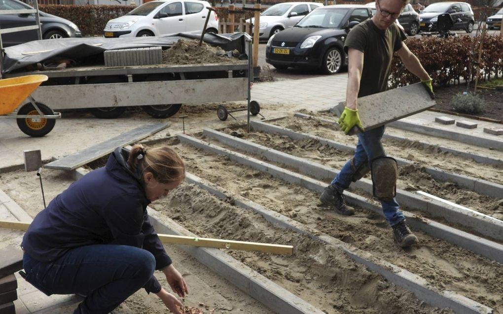 Terwijl hovenier Arjan Sikkema een laatste betonband naar zijn plek brengt legt Yvette van Dijk (gemeente Groningen) de eerste perziksteen in vernieuwde oprit.beeld Kees van Reenen