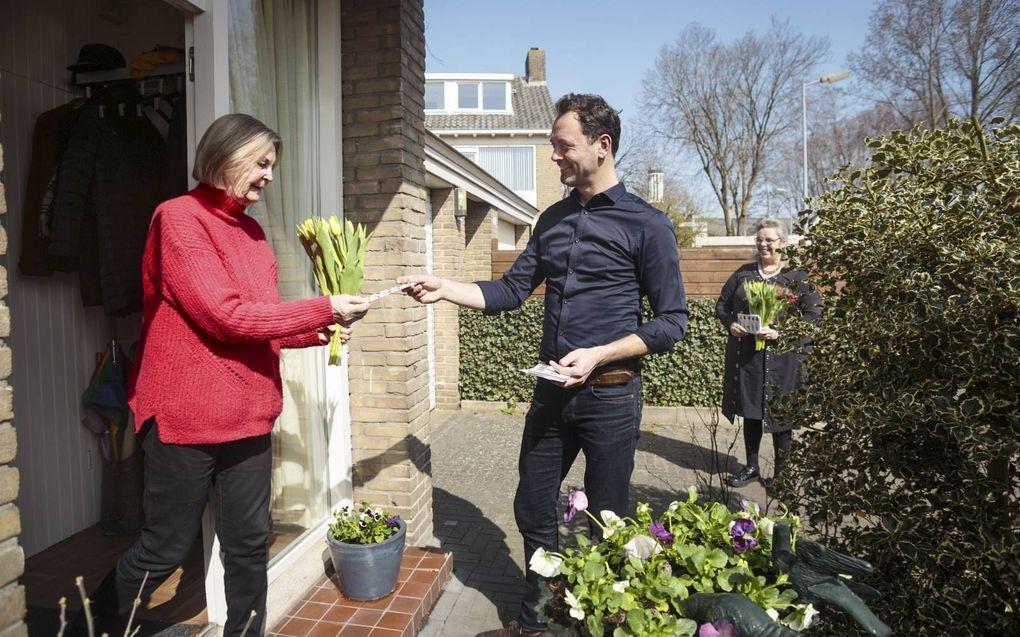 Veldwerker Jan Geerts (r.) gaat in Alkmaar bij de buren langs met een kaart met Bijbeltekst en een bosje tulpen. beeld Eran Oppenheimer