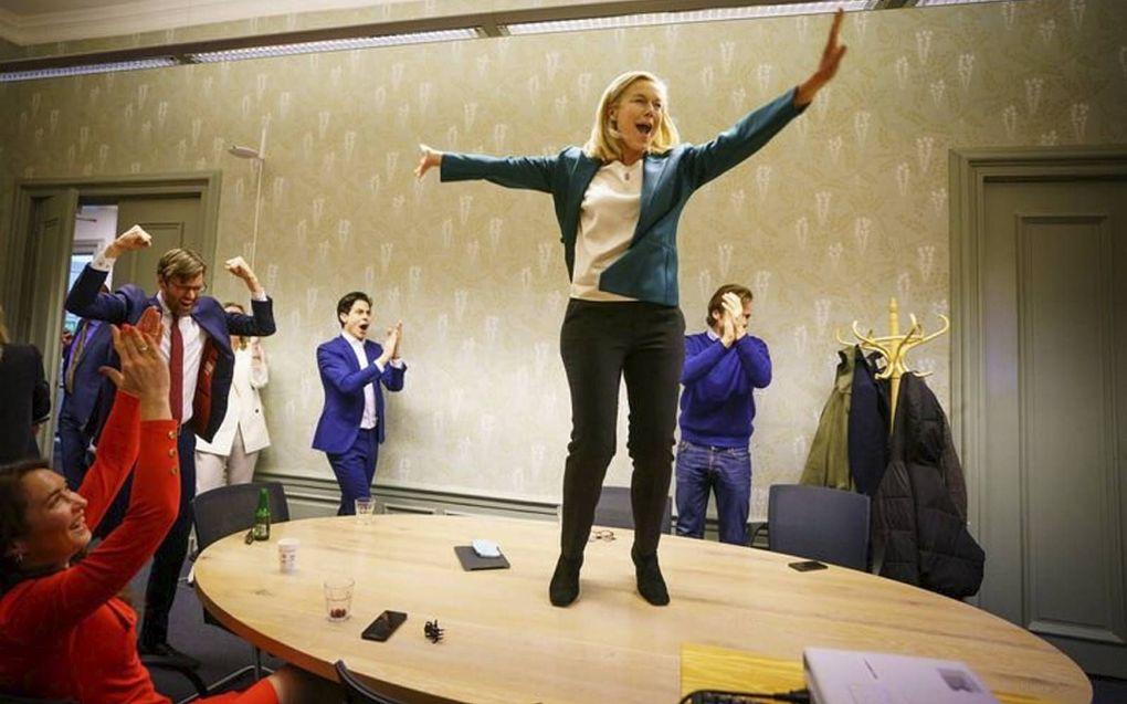D66-partijleider Sigrid Kaag danst op de tafel nadat ze verneemt dat haar partij een van de winnaars van de verkiezingen is. beeld ANP, Martijn Beekman