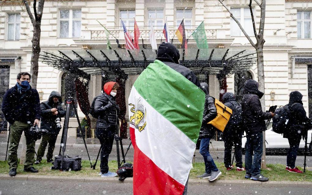 Een lid van de Iraanse oppositie betoogde dinsdag voor het Grand Hotel in Wenen, waar Iran, China en Europese partners over de nucleaire ambities van Teheran praten.beeld AFP, Joe Klamar