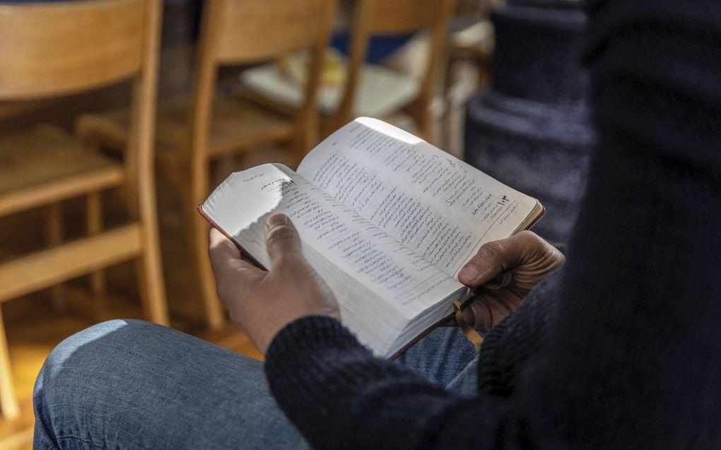 Een Iraanse asielzoeker leest de Bijbel in zijn eigen taal, het Farsi.beeld RD, Henk Visscher