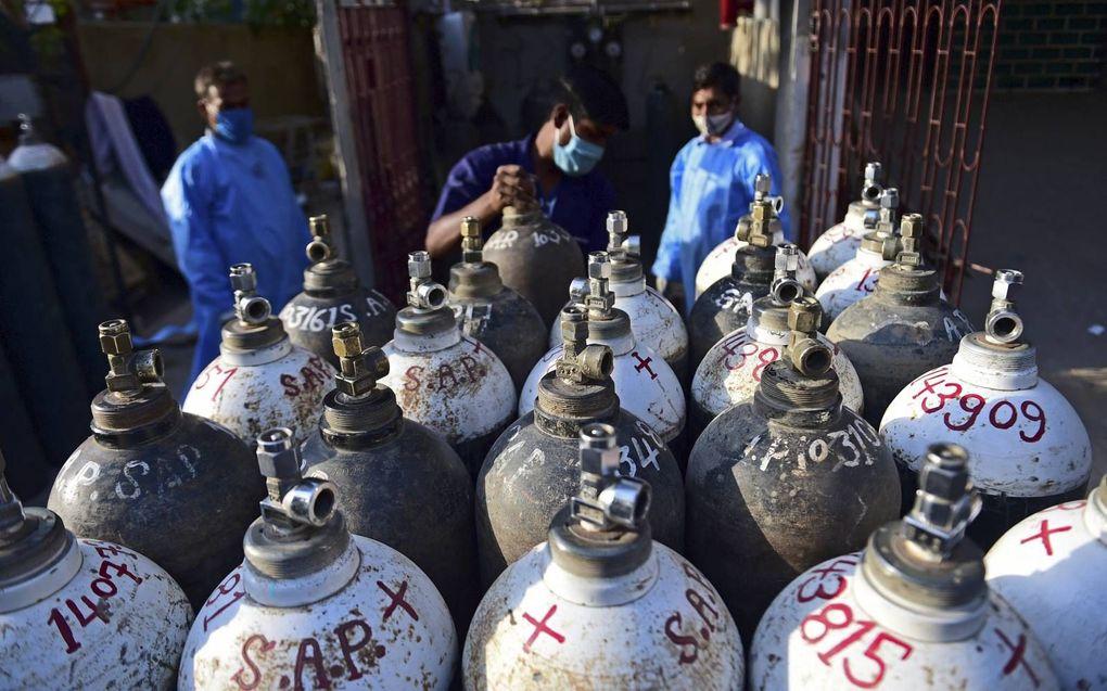 Gezondheidswerkers in de weer met zuurstofflessen, in de Noord-Indiase stad Allahabad. In veel Indiase ziekenhuizen is een nijpend tekort aan medische zuurstof. Zonder nieuwe voorraad dreigt een ramp.beeld AFP, Sanjay Kanojia