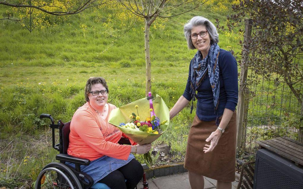 Annemieke Huijzer overhandigt een bloemetje aan haar vriendin Wilma Kooij.beeld RD, Anton Dommerholt