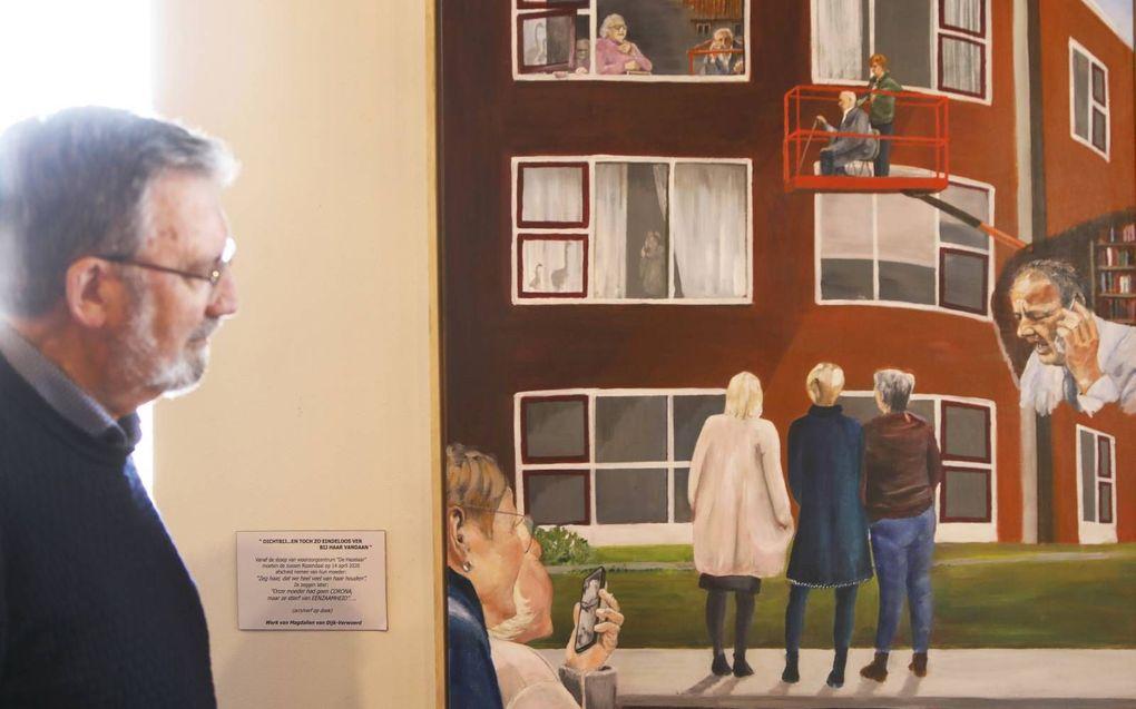 Co Mateboer bij het schilderij dat Magdalien van Dijk-Verwoerd maakte over corona. De expositie in het oude stadhuis van Genemuiden omvat twintig kunstwerken.beeld VidiPhoto