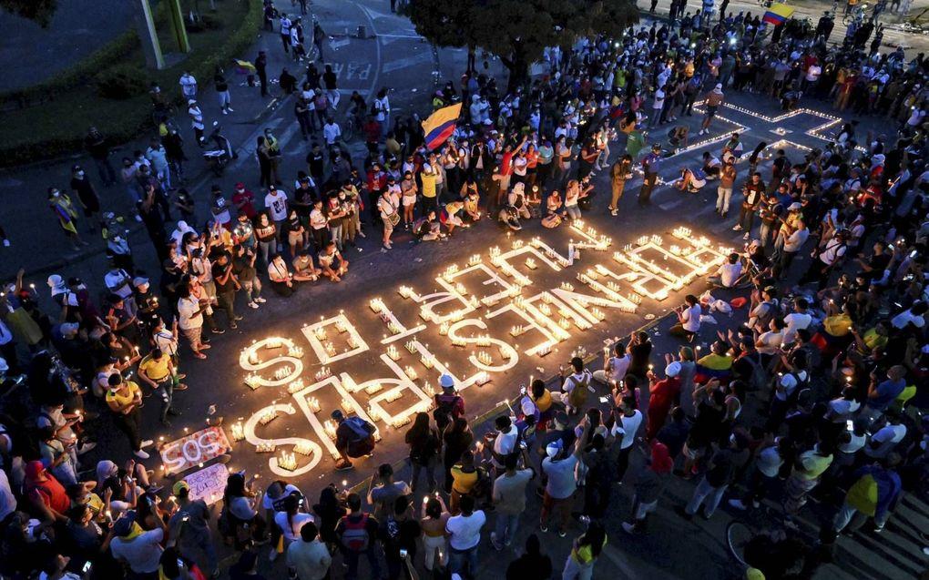 """""""Voor onze doden"""", zo luidt de tekst gevormd door kaarsen. Mensen verzamelden zich woensdag  ter nagedachtenis van de demonstranten die stierven tijdens protesten.beeld AFP, Luis Robayo"""