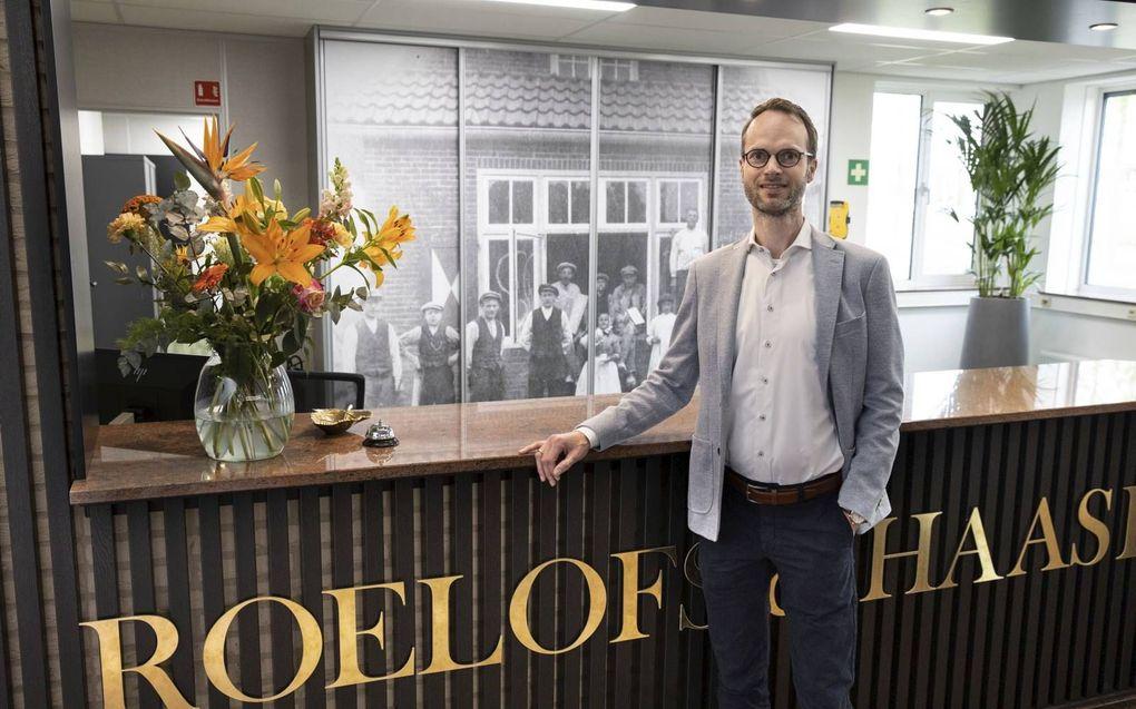 Nico Haase, de vierde directeur van bouwonderneming Roelofs & Haase, bij de receptie van het kantoor in Rijssen. Op de achtergrond een foto van de eerste klus, in 1921.