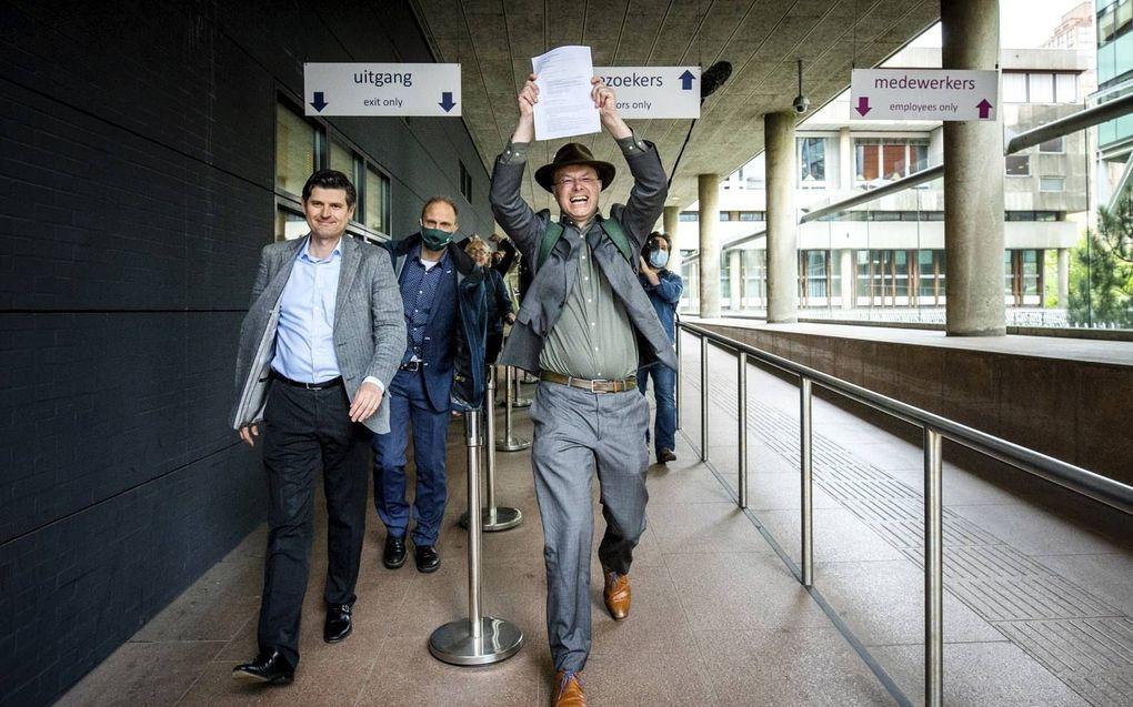 Advocaat Cox en Pols, directeur Milieudefensie, verlaten de rechtbank met de uitspraak in de hand na afloop van de klimaatzaak tegen Royal Dutch Shell.beeld ANP, Remko de Waal