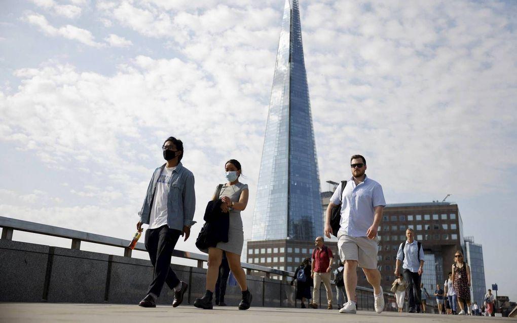 Voetgangers op de beroemde London Bridge. Hoewel de meeste coronamaatregelen maandag zijn opgeheven, zijn veel Britten sceptisch over de risico's.beeld AFP, Tolga Akmen