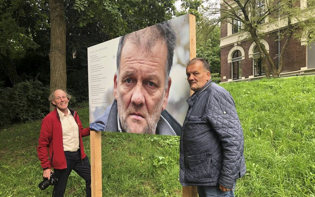 Fotograaf Ruud Spaargaren (l.) en voormalig dakloze Willem bij een bord waarop een portret van Willem is afgebeeld. beeld RD