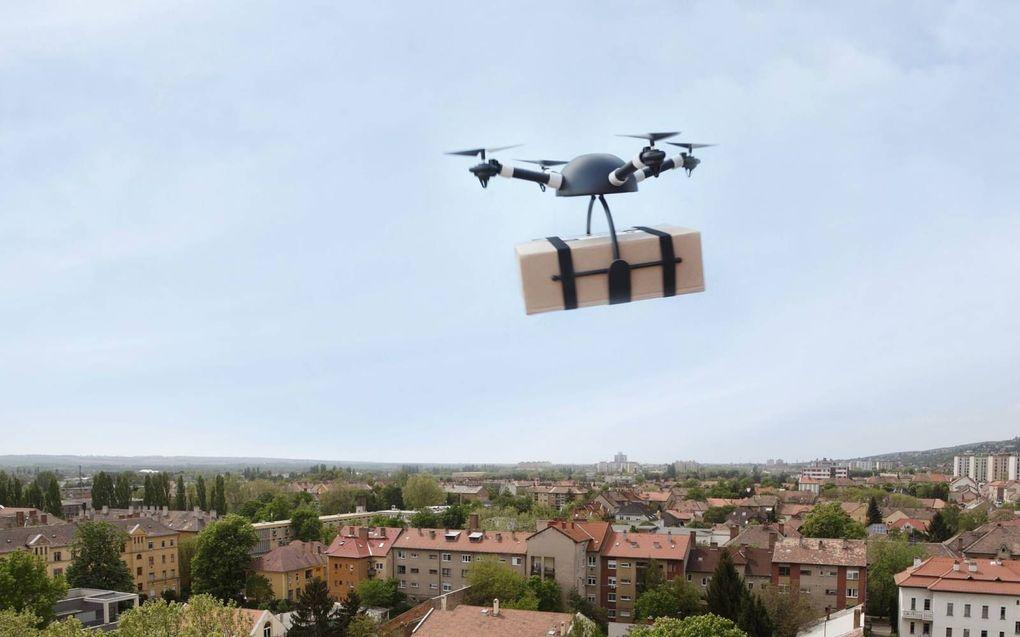 Een drone met een pakket in zijn tentakels. beeld iStock