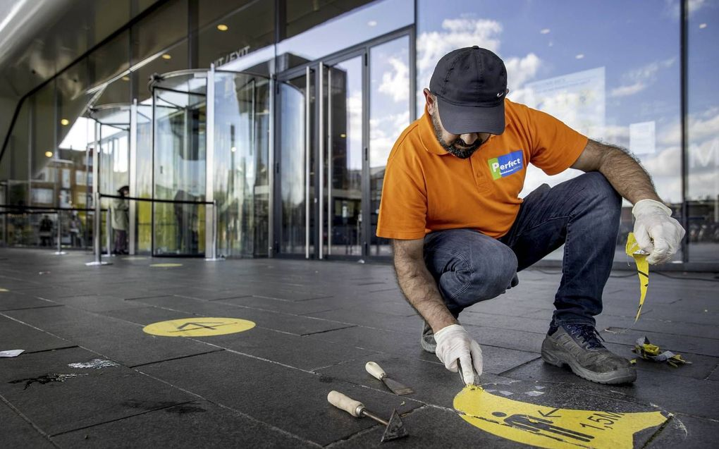 Een medewerker van het Stedelijk Museum in Amsterdam verwijdert stickers waarop bezoekers op de afstandsregel worden gewezen.beeld ANP, Koen van Weel