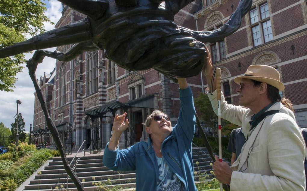 Rianne en Hannes voelen aan het lijfje van een metershoge spin, één van de kunstwerken in de tuinen van het Rijksmuseum.beeld Ronald Bakker