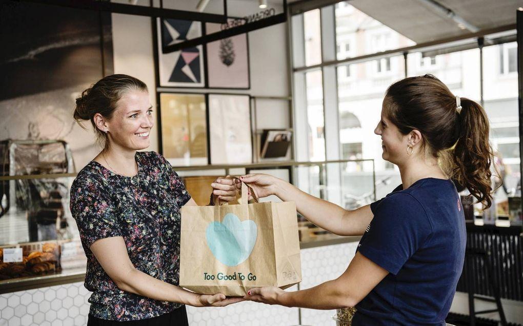 De Deense Mette Lykke, de CEO van Too Good To Go, neemt een zogenoemde magic bag in ontvangst.beeld Too Good To Go