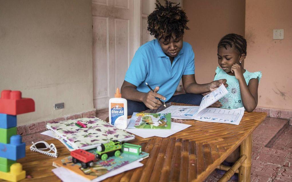De vijfjarige Lyne-Renée krijgt thuisonderwijs van haar moeder. Veel scholen in Haïti zijn al weken dicht door de politieke crisis.beeld AFP, Valérie Baeriswyl