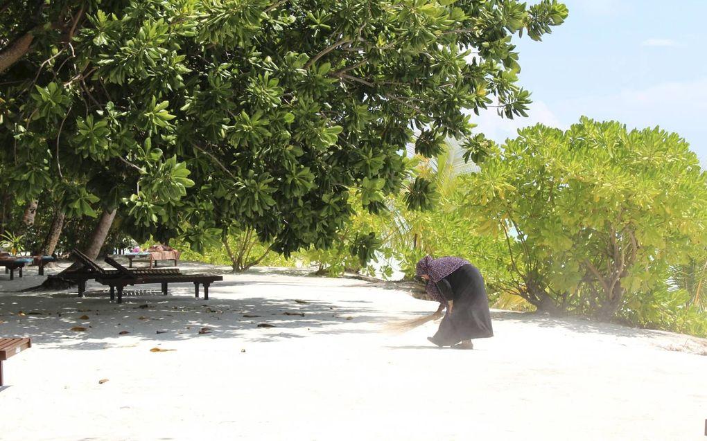 Een vrouw maakt het strand schoon op de Malediven. beeld RD