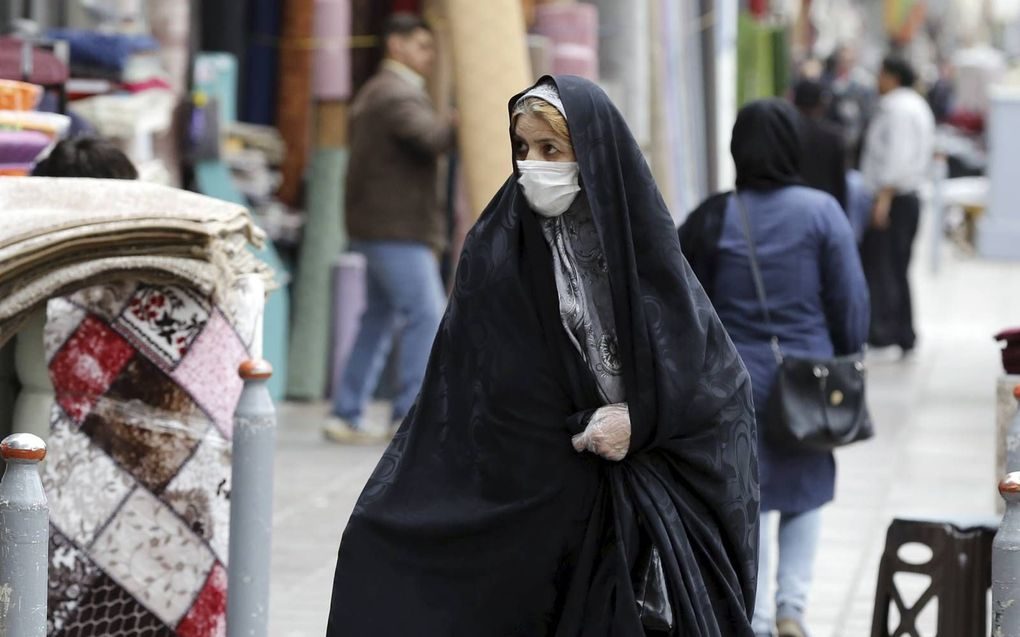 Een Iraanse vrouw draagt een gezichtsmasker en beschermende handschoenen tijdens het winkelen op de grote bazaar in Teheran.beeld EPA, Abedin Taherkenareh