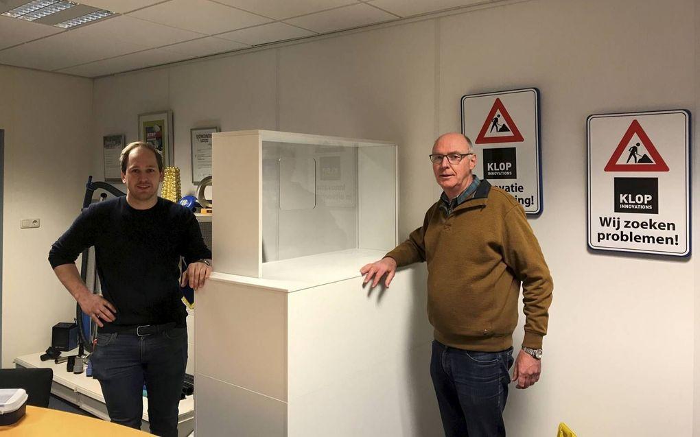 Henk Klop (r.) van Klop Innovations boog zich samen met Henk-Jan Rijksen van Rijksen Speciaal Timmerwerk en onderzoeksinstituut TNO over een balie met een afzuigsysteem. Deze moet zorgverleners effectiever beschermen tegen corona. beeld RD