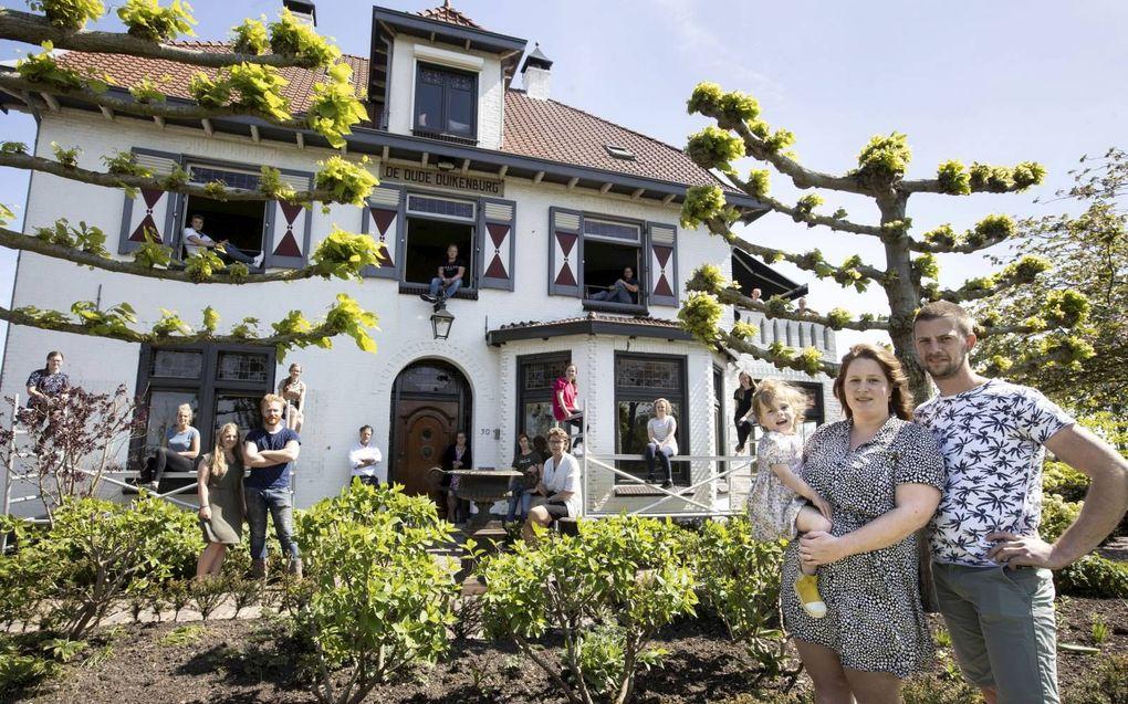Hannah en Coen Speksnijder voor hun zalenverhuurcentrum De Duikenburg in het Gelderse Echteld. Op de achtergrond staan familieleden en medewerkers.beeld Anton Dommerholt