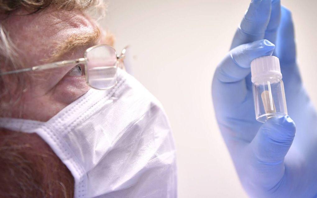 Een Britse onderzoeker bekijkt een vaccin tegen het coronavirus, dat oraal kan worden ingenomen.beeld AFP, Ben Stansall