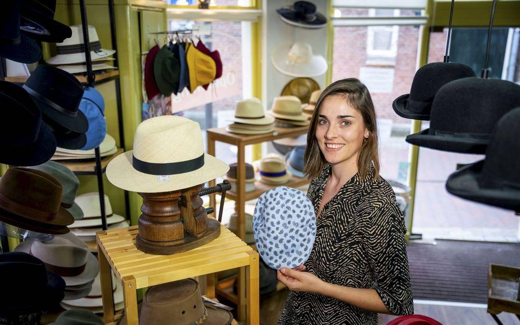 Clara van der Post poseert met een flatcap. Deze platte petten voor mannen verkopen goed, zegt ze. Volgende maand verhuist Van der Post met haar winkel naar Klaaswaal.beeld Cees van der Wal