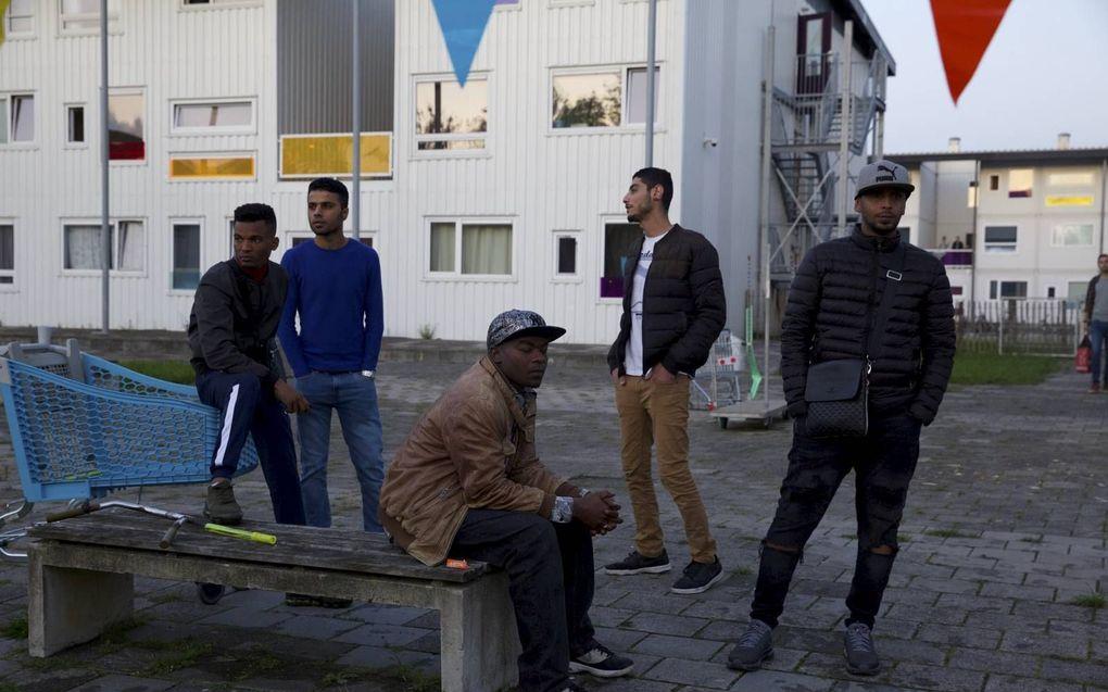 """Bewoners van Startblok Riekerhaven in Amsterdam vragen zich op een kille en regenachtige avond buiten af of een gepland """"startblokfestival"""" door zal gaan.beeld Karijn Kakebeeke"""