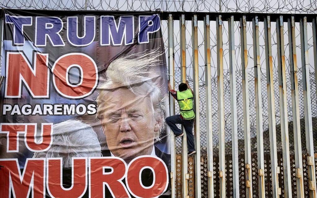 """""""Trump, wij betalen niet voor jouw muur"""", luidt de tekst op een spandoek dat Mexicanen begin dit jaar bevestigden aan een grenshek dat Mexico van de Verenigde Staten scheidt.beeld AFP, Guillermo Arias"""