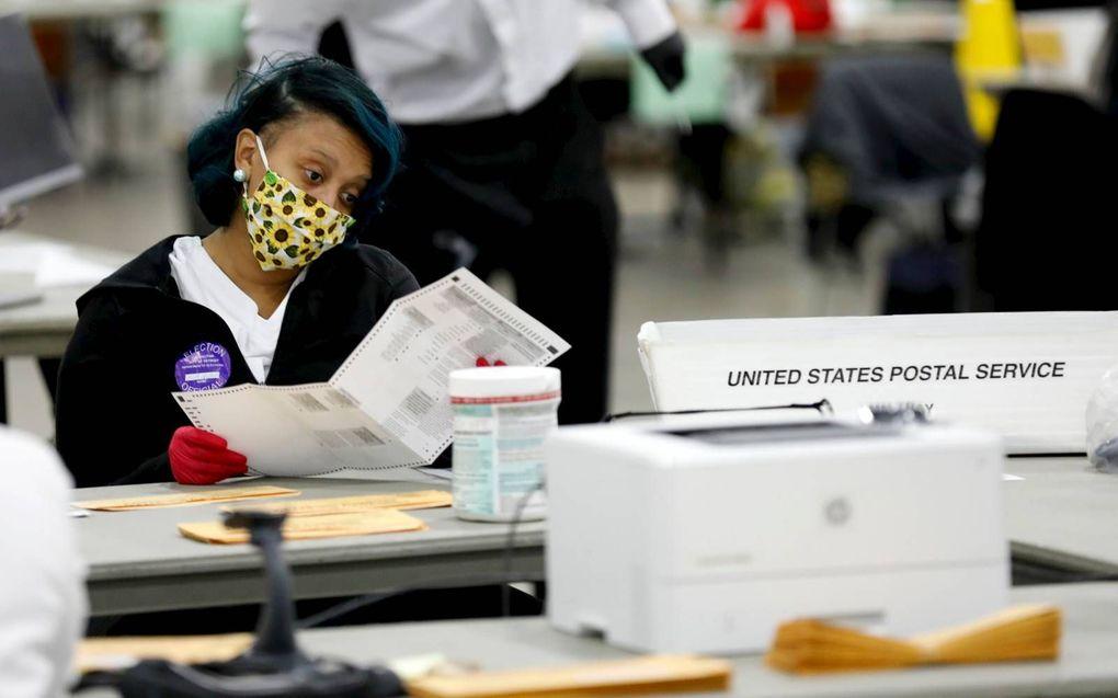 Medewerkers van een stembureau in Detroit, Michigan, waren woensdagavond nog met man en macht aan het tellen.beeld  AFP, Jeff Kowalsky