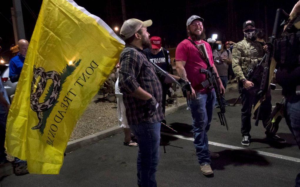 Gewapende aanhangers van president Donald Trump verzamelden zich donderdagavond bij een kantoor in Phoenix, Arizona, om te eisen dat alle stemmen zouden worden geteld.beeld EPA, Rick d'Elia