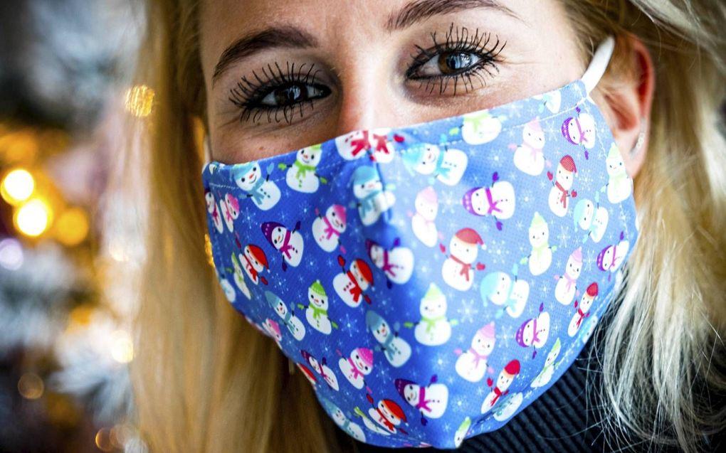 Een vrolijk kerstmondkapje. De meeste wetenschappers wereldwijd zijn het er over eens dat zelfs niet-medische mondkapjes de overdracht van het coronavirus helpen tegengaan.beeld ANP, Rob Engelaar