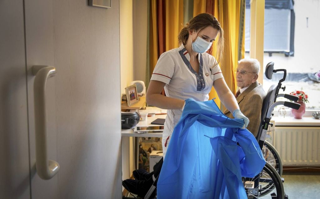 Saskia van der Lede, waarnemend afdelingscoördinator van de Wijnrank in verpleeghuis Salem, en mijnheer Kik, bewoner van die afdeling. beeld RD, Henk Visscher