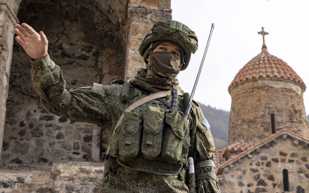 Een Russische soldaat in de tuin van het Dadivankklooster in Kalbajar, Nagorno-Karabach.beeld AFP, Andrey Borodulin