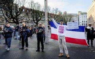 Aanhangers van de groep Viruswaarheid houden uit onvrede met de coronamaatregelen een Nederlandse vlag ondersteboven. beeld ANP, Bart Maat