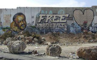 Afbeelding van Barghouti op de barrière ten noorden van Jeruzalem. beeld Alfred Muller