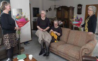 Hendrika Mourik en Gerita ten Bolscher overhandigen een bloemetje aan handwerksters Anja van de Belt en Ina Haase uit Rijssen.beeld RD, Anton Dommerholt