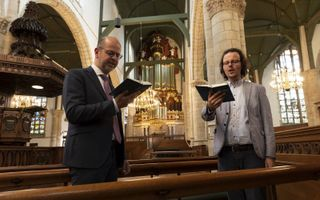 Ds. M. C. Batenburg (l.) en kerkorganist Gerben Budding zijn blij dat in de Sint Jan in Gouda weer honderden mensen kunnen samenkomen en zingen. beeld Martin Droog