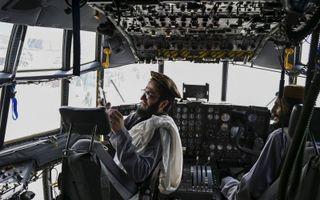Een talibanstrijder maakt een selfie in de cockpit van een buitgemaakt transporttoestel van de Afghaanse luchtmacht. beeld AFP, Wakil Kosar