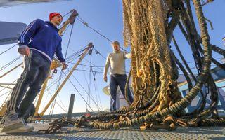In Harlingen wordt de UK 227 omgebouwd van elektrisch vissen naar de verouderde boomkortechniek. Foto: schipper Simon van Slooten (r.) en bemanningslid Evert de Boer helpen bij het takelen van de pulsmodules. beeld Simon Bleeker