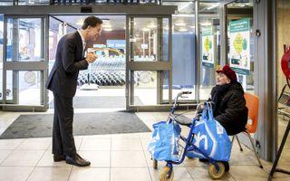 Premier Mark Rutte praatte donderdag met een klant van de Albert Heijn in Den Haag. beeld ANP, Remko de Waal