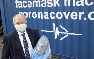 Jan van Tienhoven poseert met twee van zijn uitvindingen: het mondkapje in de speciale houder en de volgelaatsmasker.beeld RD, Anton Dommerholt