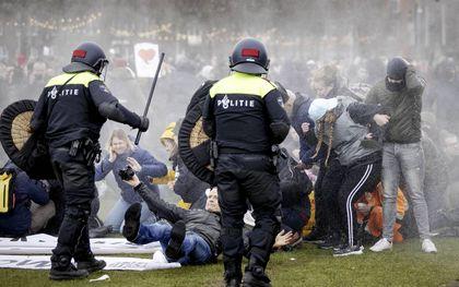 De politie veegde zondag het Museumplein in Amsterdam leeg. Ook elders in het land kwam het afgelopen weekend tot onlusten uit protest tegen de avondklok. beeld ANP, Robin van Lonkhuijsen