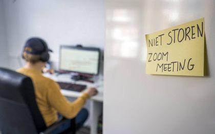 Een werknemer doet op zijn kamertje thuis mee aan een videovergadering. Hij wil niet worden afgeleid. beeld ANP, Lex van Lieshout
